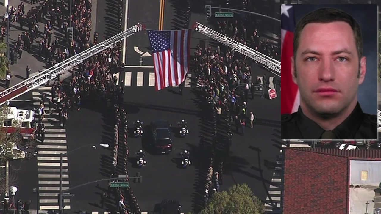 The funeral procession for fallen San Jose Officer Michael Johnson passes underneath an American flag in San Jose, Calif. on April 2, 2015.