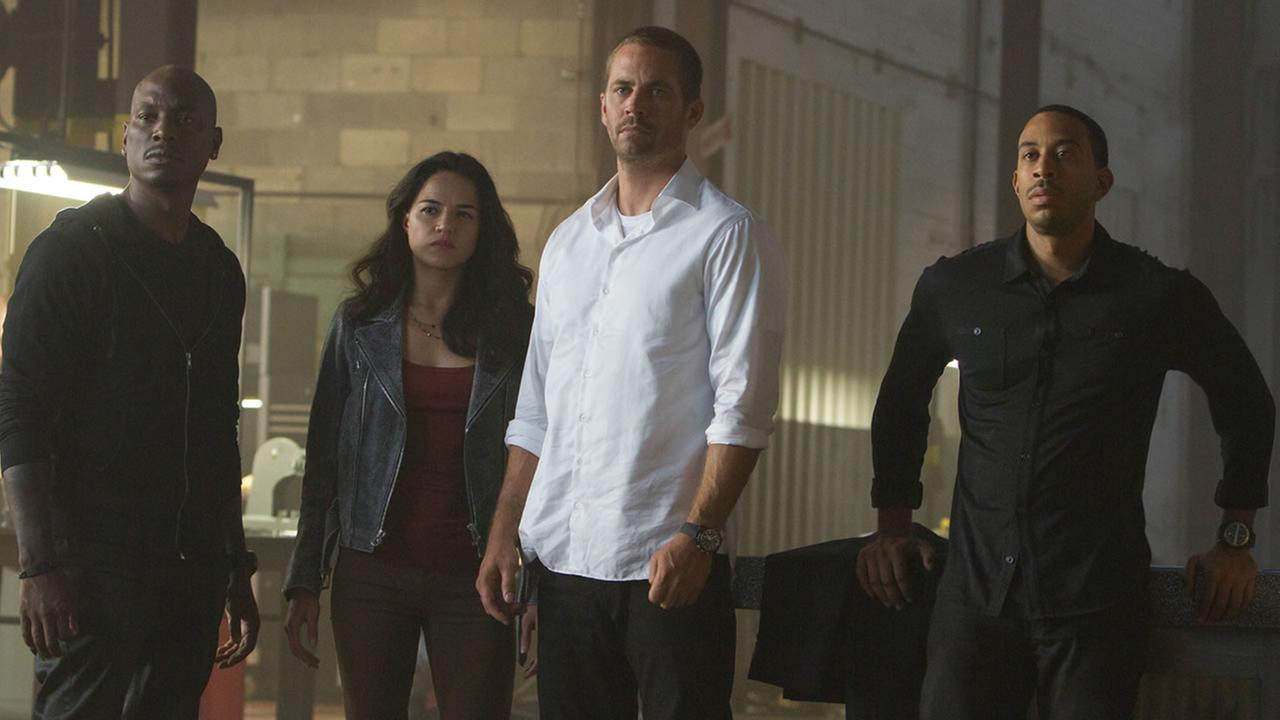 This photo shows, from left, Tyrese Gibson as Roman, Michelle Rodriguez as Letty, Paul Walker as Brian, and Chris Ludacris as Tej, in a scene from Furious 7. (AP Photo/Universal Pictures, Scott Garfield)