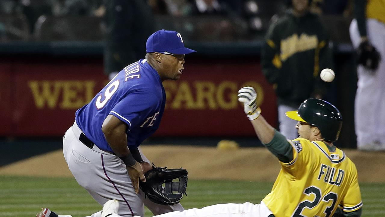 Oakland Athletics Sam Fuld (23) slides in for a triple as Texas Rangers third baseman Adrian Beltre