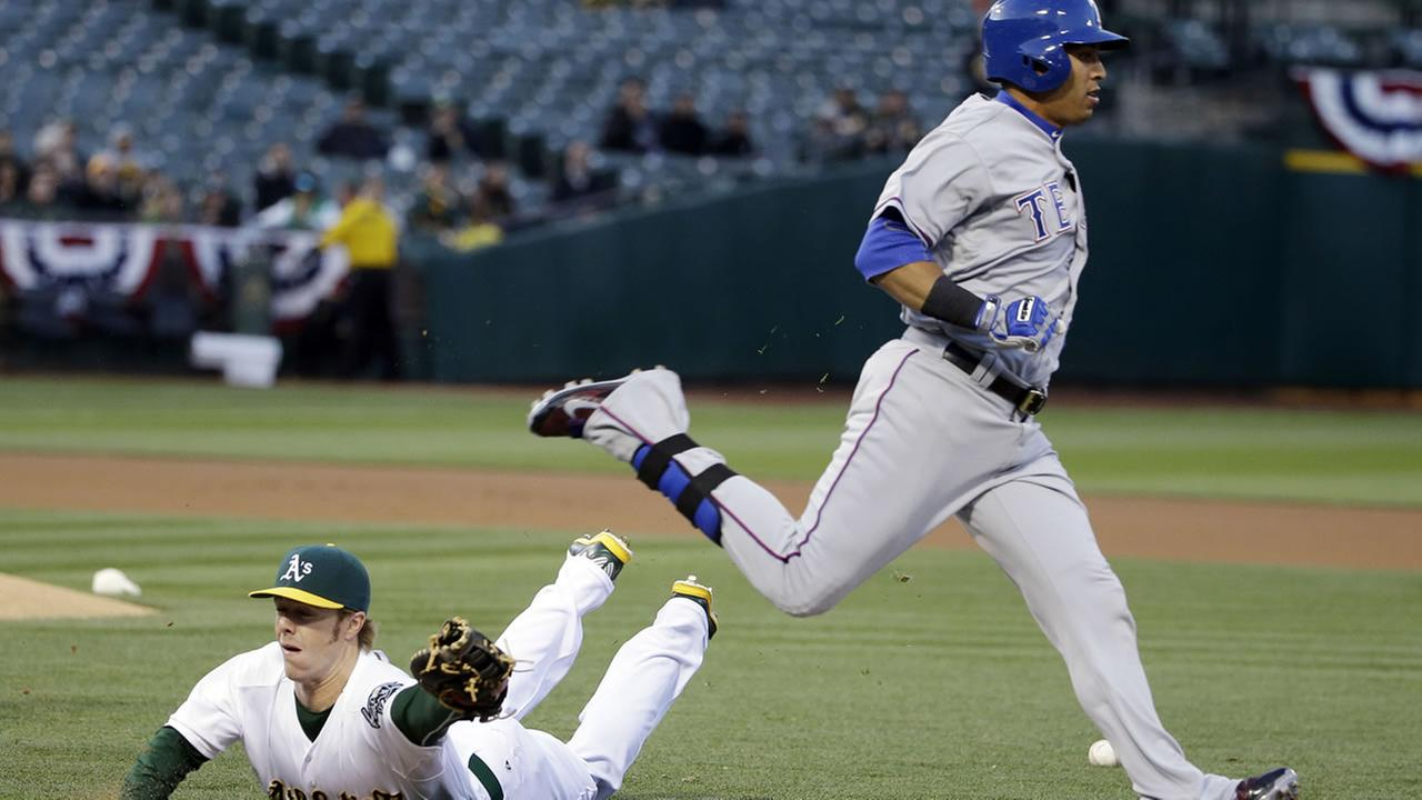 Texas Rangers Leonys Martin, right, runs past Oakland Athletics first baseman Mark Canha after a bunt during the first inning of a baseball game Wednesday, April 8, 2015.