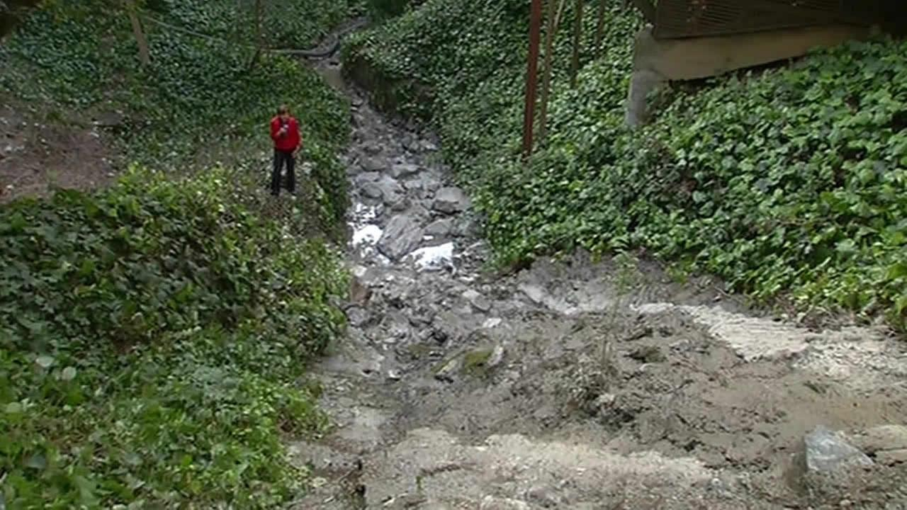 ABC7 News reporter Laura Anthony stands next to a creek in Oakland, Calif. that was emptied after cement flowed into it on April 8, 2015.KGO-TV