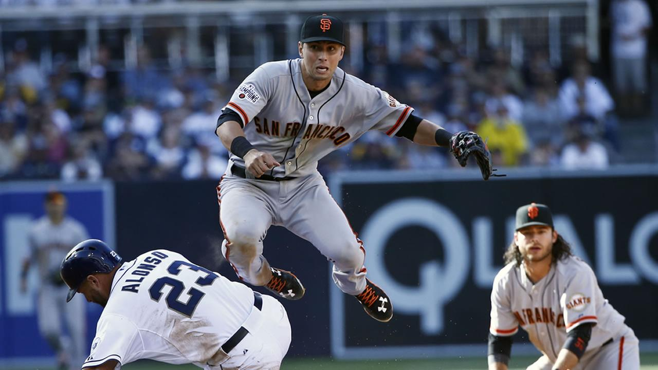 Giants second baseman Joe Panik hurdles Padres Yonder Alonso while relaying to first to complete a double play in the fifth inning of a baseball game Thursday, April 9, 2015.