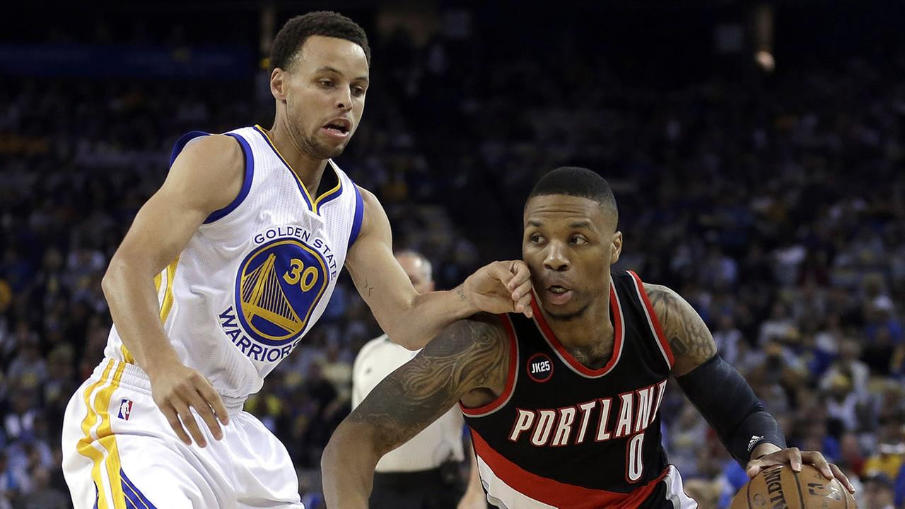 Portland Trail Blazers Damian Lillard, right, drives the ball against Golden State Warriors Stephen Curry