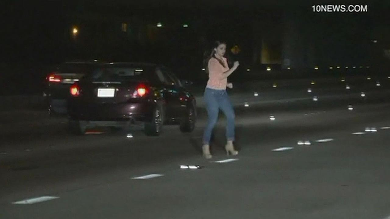 woman runs across I-15