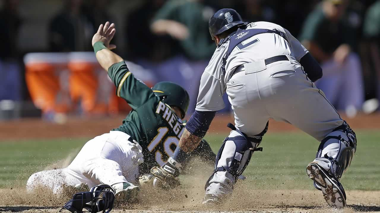 Seattle Mariners catcher Jesus Sucre tags out Oakland Athletics Josh Phegley in the seventh inning  on Saturday, April 11, 2015 in Oakland, Calif.(AP Photo/Ben Margot)