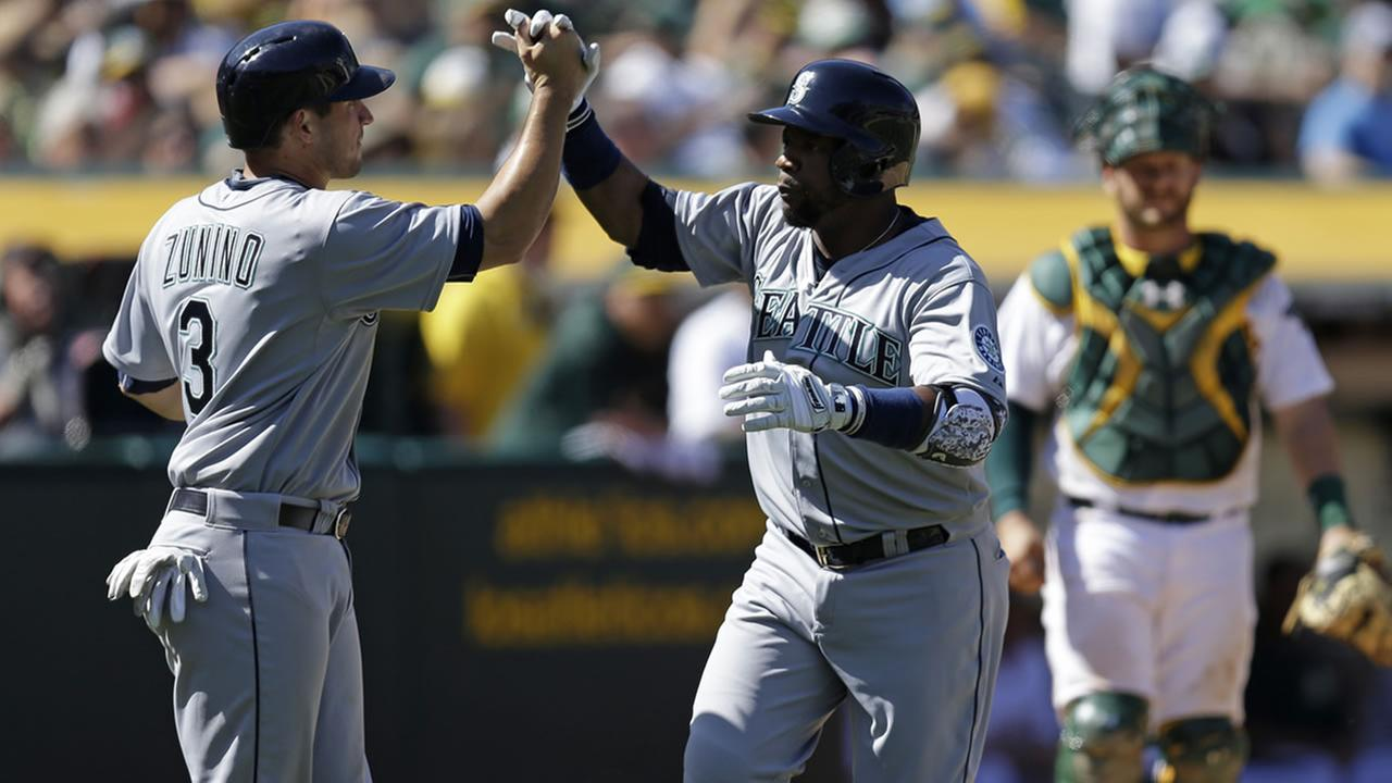Mariners Rickie Weeks is congratulated by Mike Zunino after hitting a three-run home run off Athletics Eric OFlaherty on April 12, 2015, in Oakland, Calif. (AP Photo)