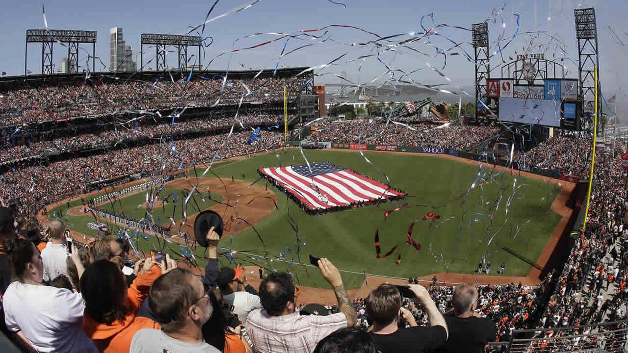 Fans cheer as confetti falls after the national anthem before the San Francisco Giants home opener baseball game against the Colorado Rockies in San Francisco, April 13, 2015. (AP Photo/Eric Risberg)