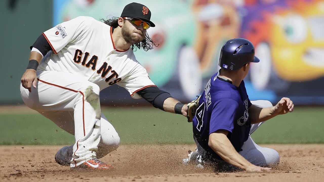 San Francisco Giants shortstop Brandon Crawford, left, tags out Colorado Rockies Nick Hundley during the third inning of a baseball game in San Francisco, April 13, 2015. (AP Photo/Eric Risberg)