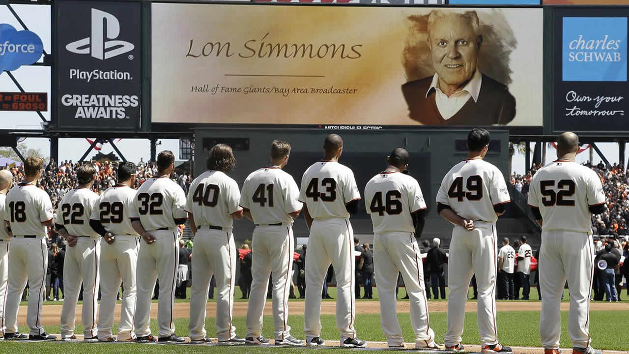 San Francisco Giants players stand as former announcer Lon Simmons, who died on April 5, 2015, is honored before a game in San Francisco, April 13, 2015. (AP Photo/Eric Risberg)