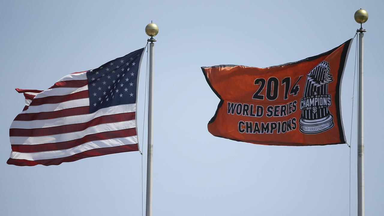 The San Francisco Giants 2014 championship pennant is raised at AT&T Park before a game in San Francisco, April 13, 2015. (AP Photo/Eric Risberg)