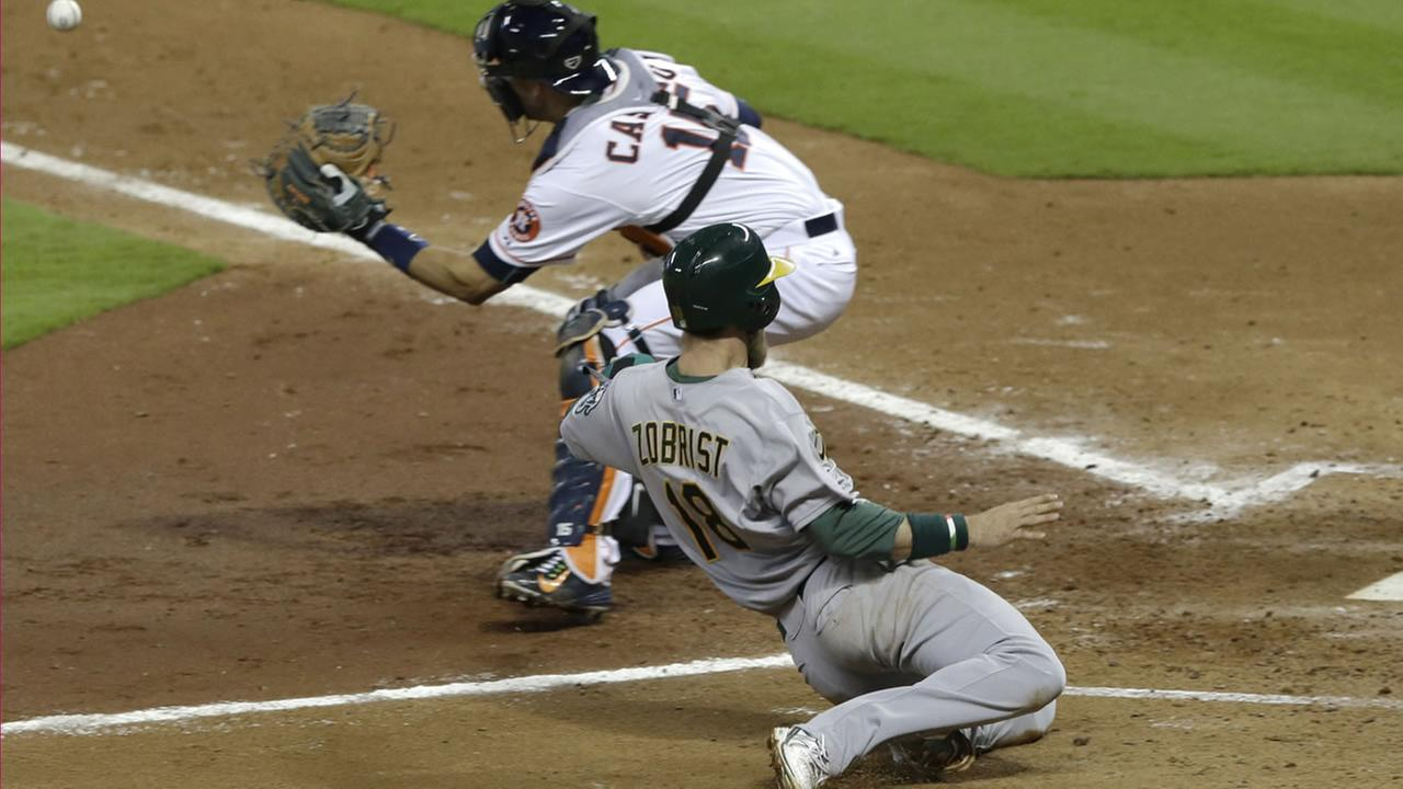 Oakland Athletics Ben Zobrist (18) slides to home plate to score on a Billy Butler double as Houston Astros catcher Jason Castro