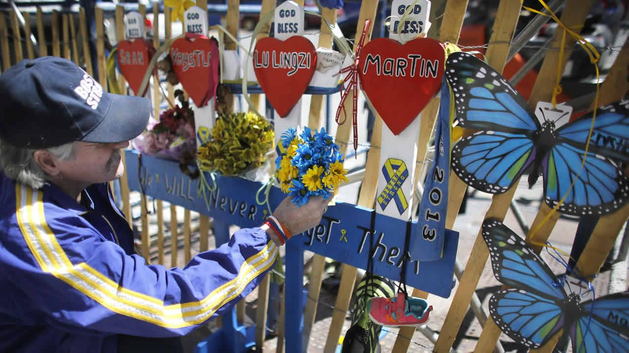 Kevin Brown, of Brockton, Mass., attaches flowers to a memorial near one of two blast sites near the finish line of the Boston Marathon, April 15, 2015, in Boston. (AP Photo/Steven Senne)