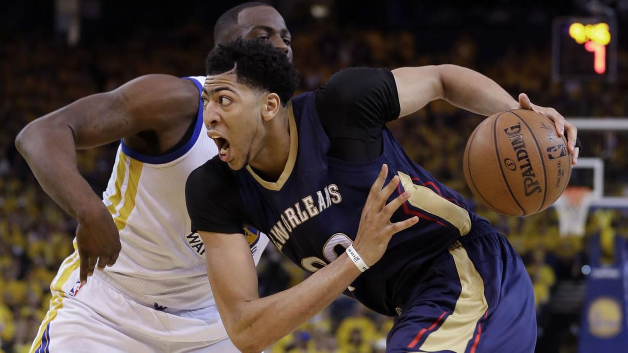 Pelicans Anthony Davis, right, drives past Warriors Draymond Green during the second half in Game 1 of the NBA basketball playoffs Saturday, April 18, 2015. (AP Photo)
