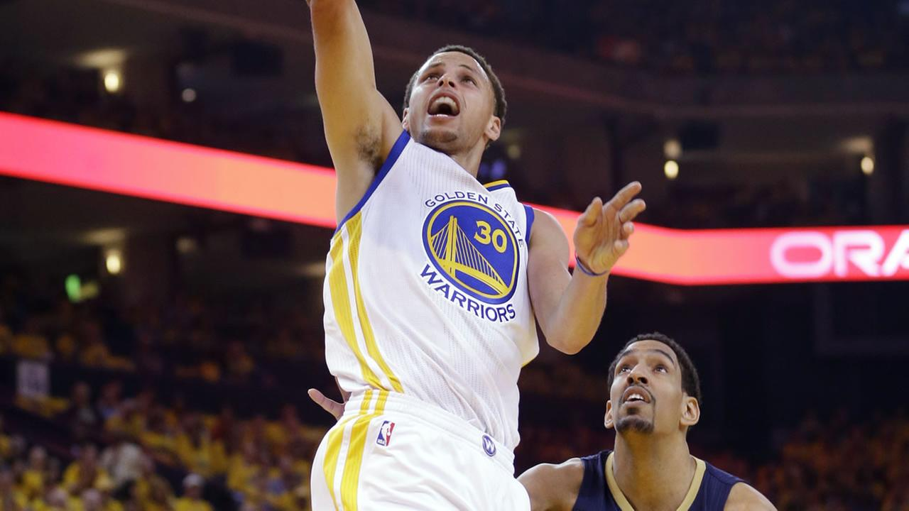 Warriors Stephen Curry (30) scores past Pelicans Alexis Ajinca during Game 1 of the NBA basketball playoffs on April 18, 2015, in Oakland, Calif. (AP Photo)