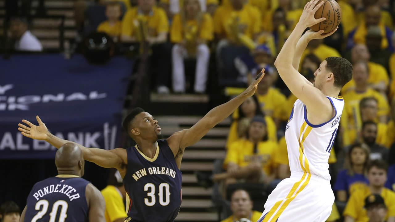 Golden State Warriors Klay Thompson shoots over New Orleans Pelicans Norris Cole and Quincy Pondexter during Game 1 of the NBA playoffs April 18, 2015, in Oakland, Calif. (AP Photo/Marcio Jose Sanchez)AP Photo/Marcio Jose Sanchez
