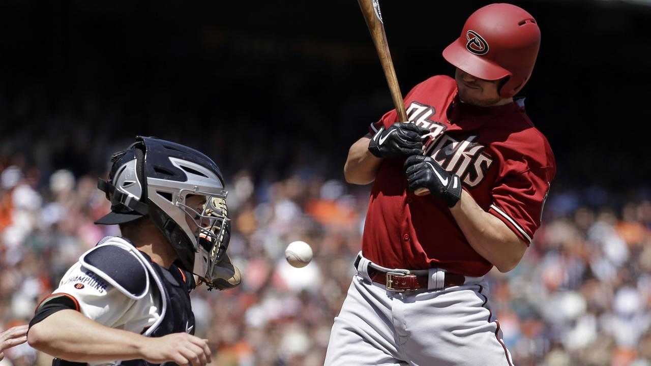 Diamondbacks Jordan Pacheco, right, is hit by a pitch thrown by Giants Tim Hudson in the third inning of a baseball game Sunday, April 19, 2015, in San Francisco. (AP Photo)