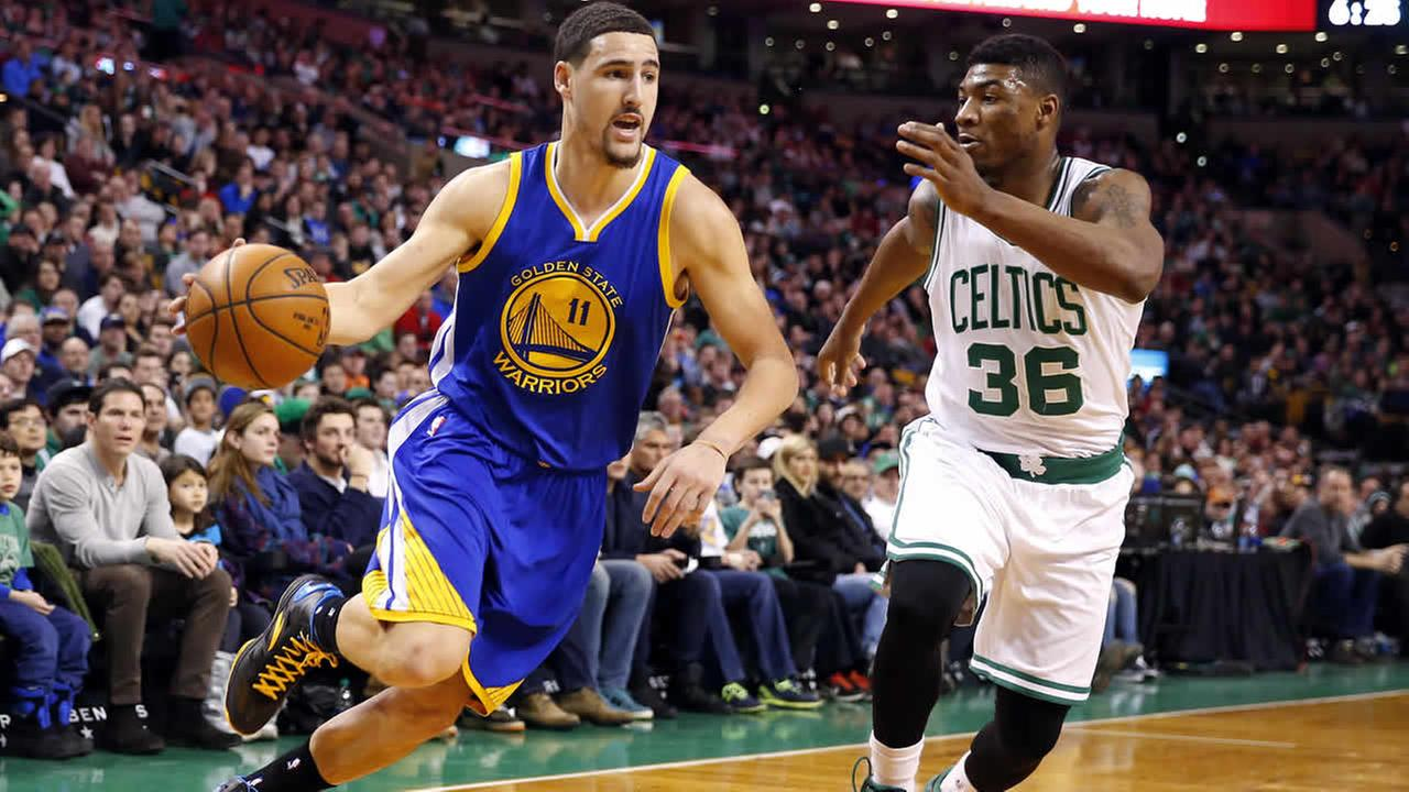Golden State Warriors Klay Thompson drives on Boston Celtics Marcus Smart during the first quarter of an NBA basketball game in Boston Sunday, March 1, 2015. (AP Photo/Winslow Townson)