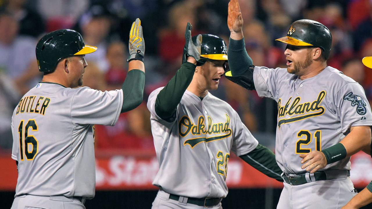 Oakland Athletics Stephen Vogt, right, is congratulated by Billy Butler, left, and Mark Canha