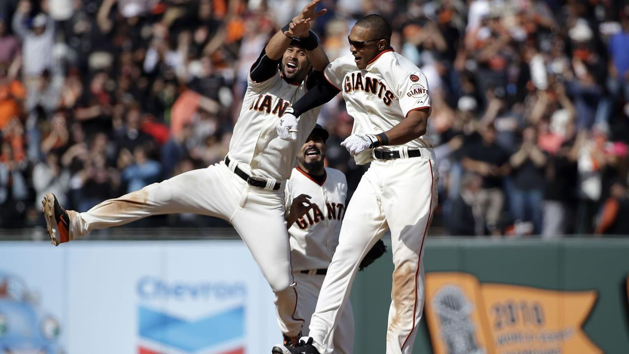 San Francisco Giants including Nori Aoki, of Japan, left, and Brandon Belt (9) mob teammate Joe Panik after Panik hit an RBI sacrifice fly which scored the game winning run.