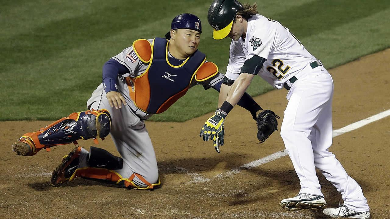 Houston Astros catcher Hank Conger, left, tags out Oakland Athletics Josh Reddick in the tenth inning of a baseball game on April 25, 2015, in Oakland, Calif. AP Photo/Ben Margot)