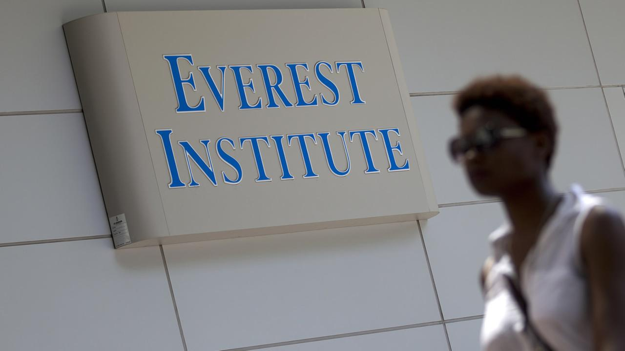 In this July 8, 2014 file photo, a woman walks past the Everest Institute in Silver Spring, Md. (AP Photo/Jose Luis Magana, File)