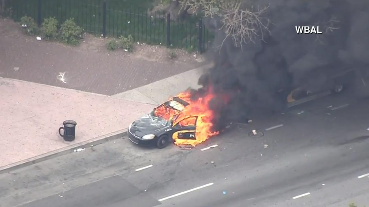 A police car was set on fire during a protest in Baltimore on April 27, 2015.