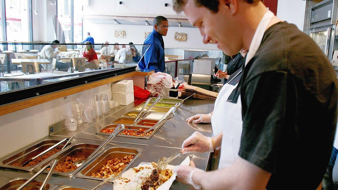 Chipotle manager Ryan OToole piles on the ingredients on a chicken burritio, Chipotles most popular item, at a downtown Denver location on Monday, May 8, 2006. (AP Photo)