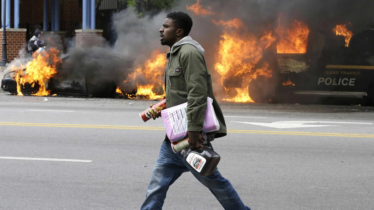 A man carries items from a store as police vehicles burn, Monday, April 27, 2015, after the funeral of Freddie Gray in Baltimore. (AP Photo/Patrick Semansky)