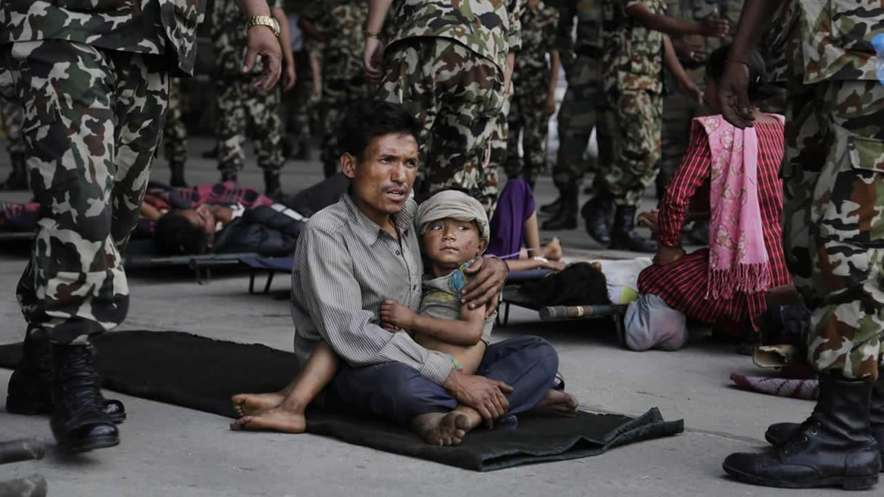 A man sits with a child on his lap as victims of Saturdays earthquake, wait for ambulances after being evacuated at the airport in Kathmandu, Nepal, April 27, 2015. (AP Photo/Altaf Qadri)