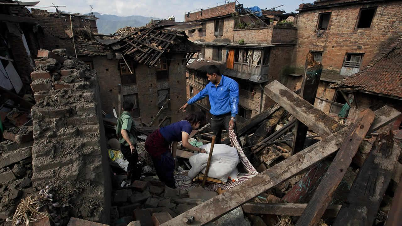 A Nepalese family collects belongings from their home destroyed in Saturdays earthquake, in Bhaktapur on the outskirts of Kathmandu, Nepal, April 27, 2015. (AP Photo/Niranjan Shrestha)
