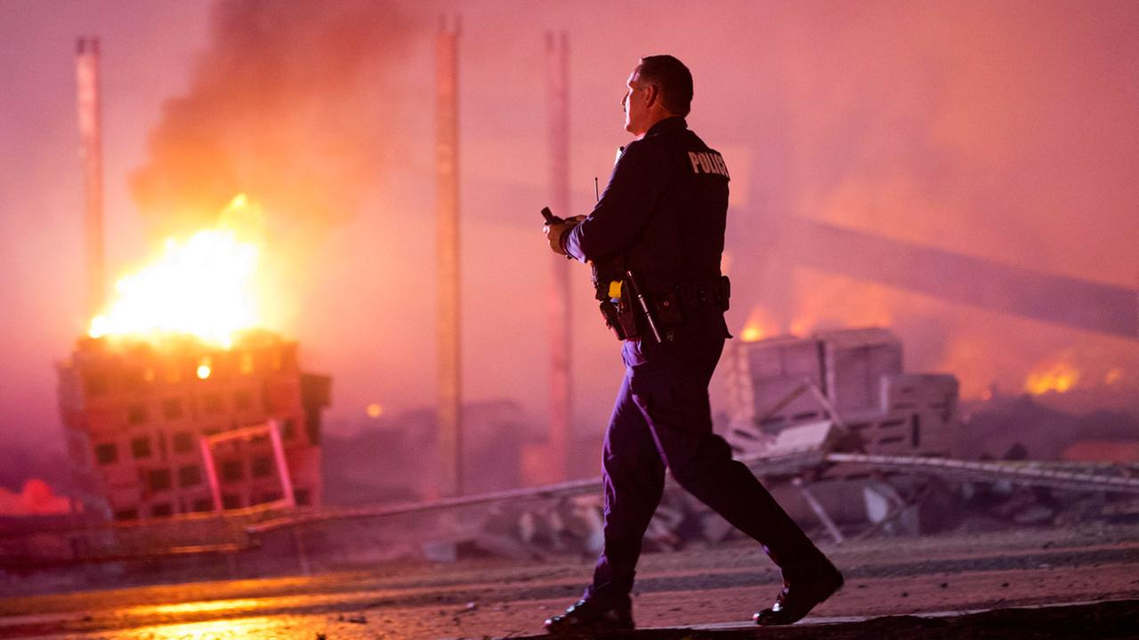 A police officer walks by a blaze after rioters plunged part of Baltimore into chaos, Monday, April 27, 2015.