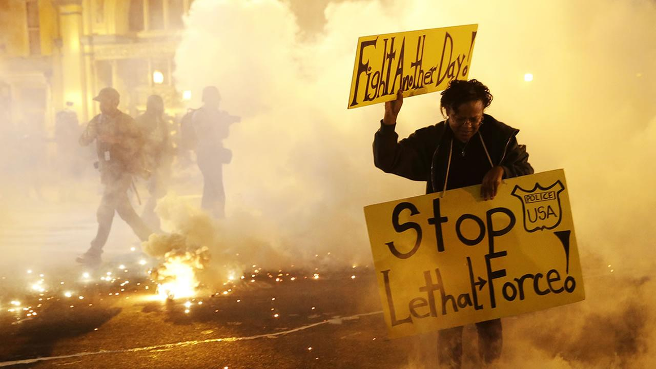 woman in Baltimore runs for safety as police throw tear gas canisters