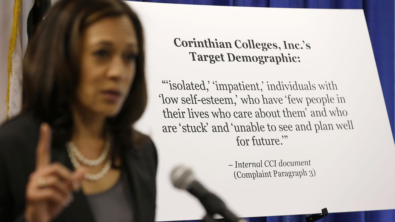 California Attorney General Kamala Harris gestures while standing by a display showing the target demographic of Corinthian Colleges.