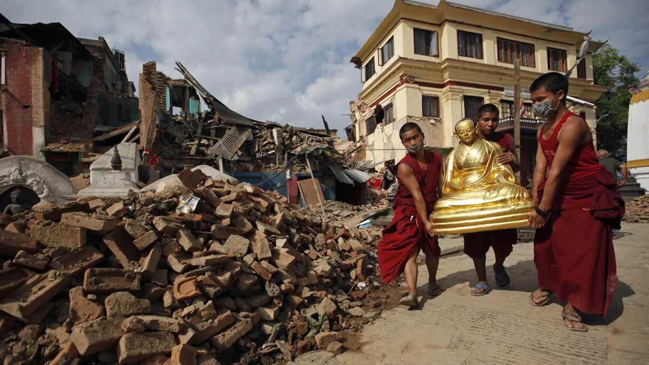 Buddhist monks salvage a statue from a monastery around the famous Swayambhunath stupa after it was damaged by Saturdays earthquake in Kathmandu, Nepal, April 30, 2015. (AP Photo/Niranjan Shrestha)