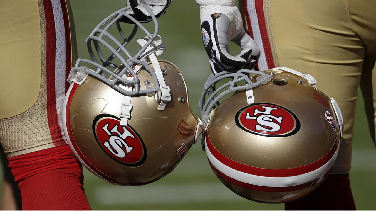 two San Francisco 49ers players hold their helmets