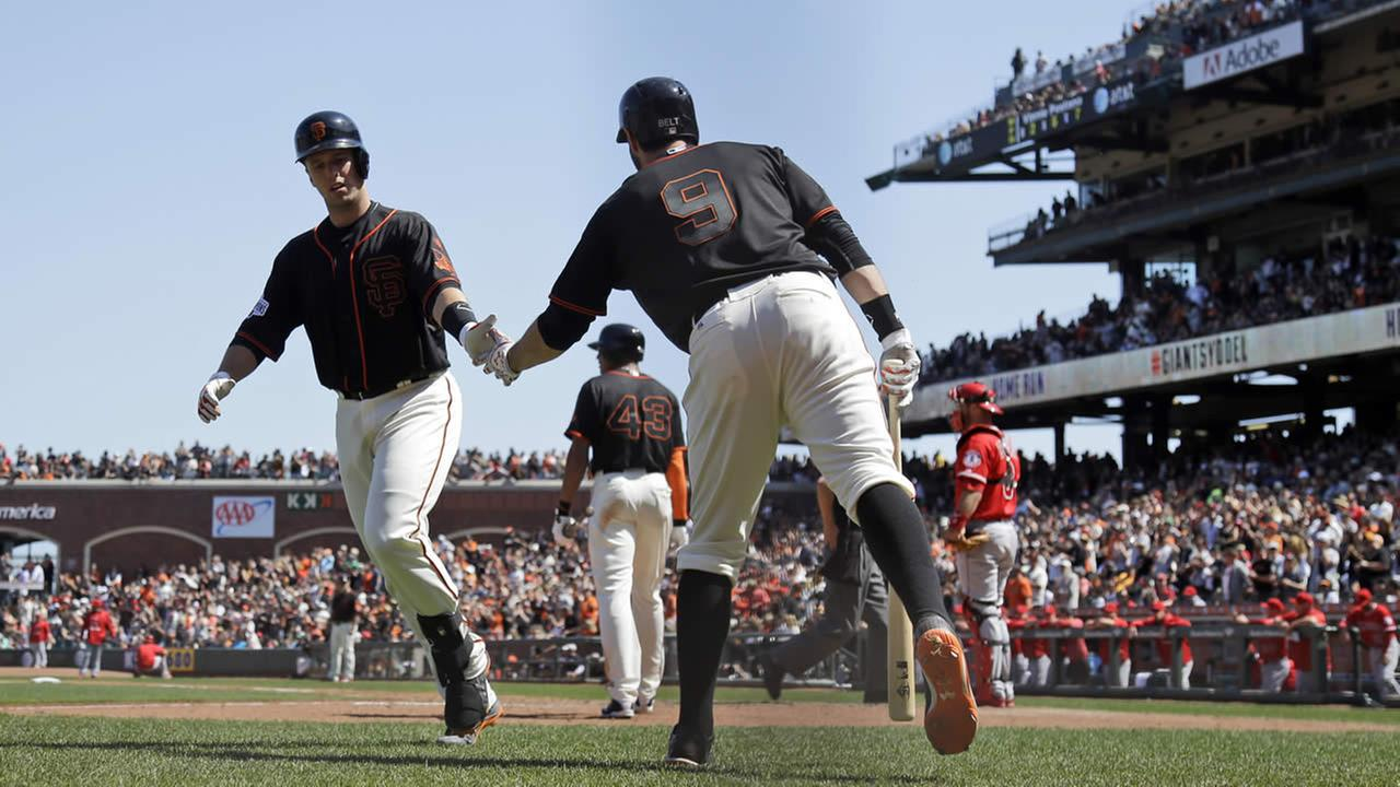 Giants Buster Posey celebrates his solo home run with teammate Brandon Belt during the seventh inning of a baseball game on Saturday, May 2, 2015, in San Francisco. (AP Photo)