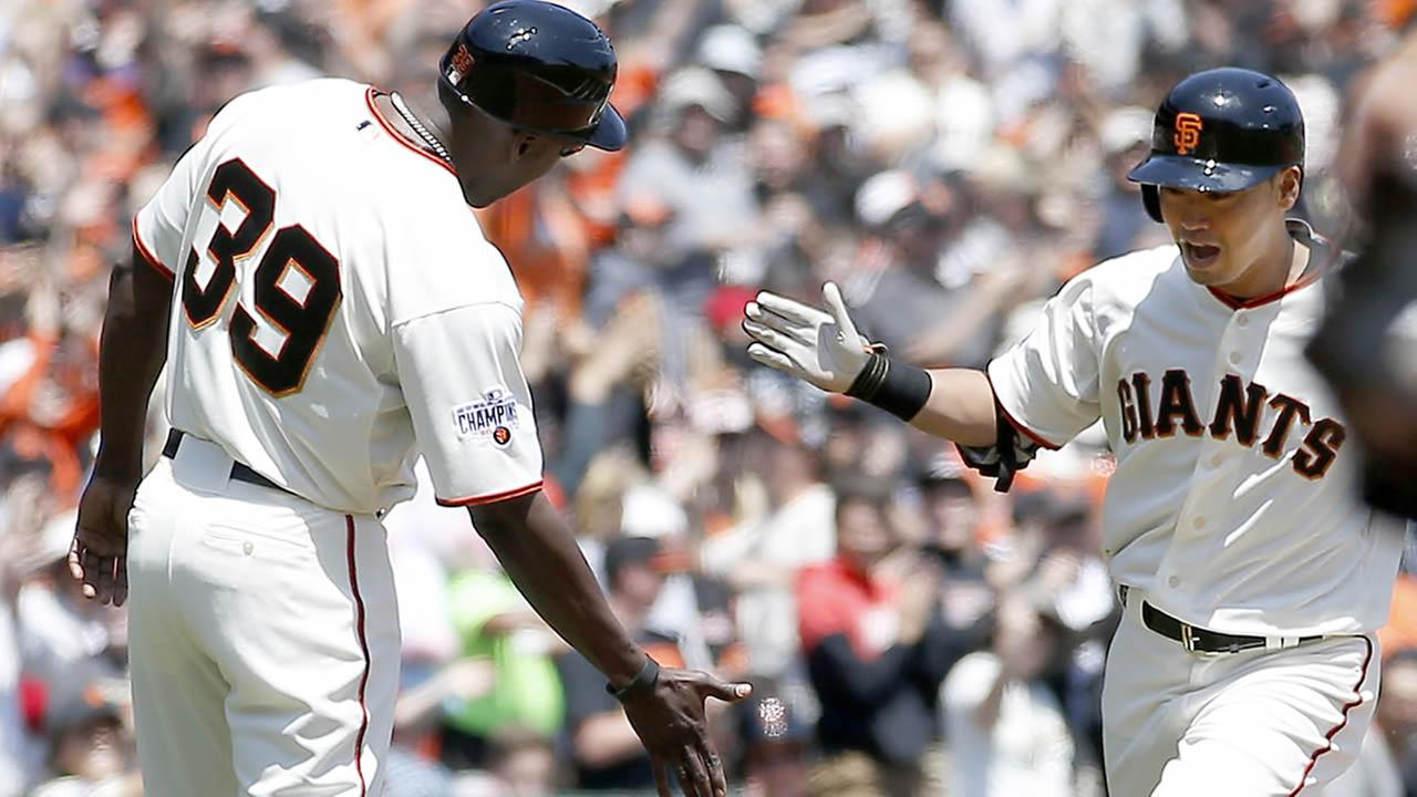 Giants third base coach Roberto Kelly congratulates Nori Aoki after he hit a solo home run against the Angels during a baseball game on May 3, 2015. (AP Photo/Tony Avelar)