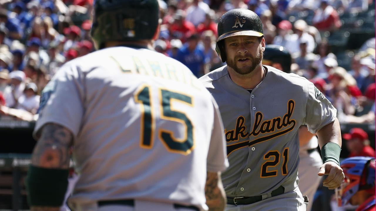 Oakland Athletics Stephen Vogt is congratulated by Brett Lawrie following his solo home run against the Texas Rangers during a game on May 3, 2015. (AP Photo)