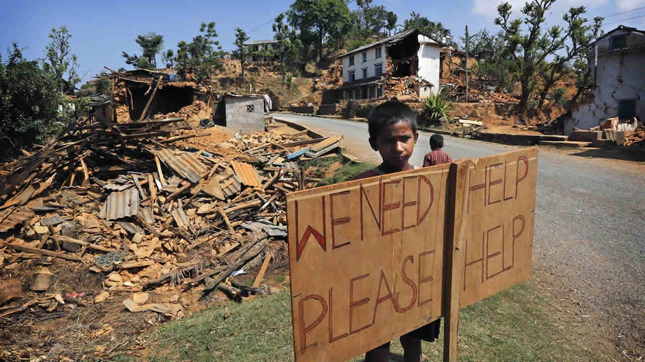 A Nepalese boy stands outside his village with a signboard asking for help in Pauwathok village, Sindhupalchok district, Nepal, May 2, 2015. (AP Photo / Manish Swarup)