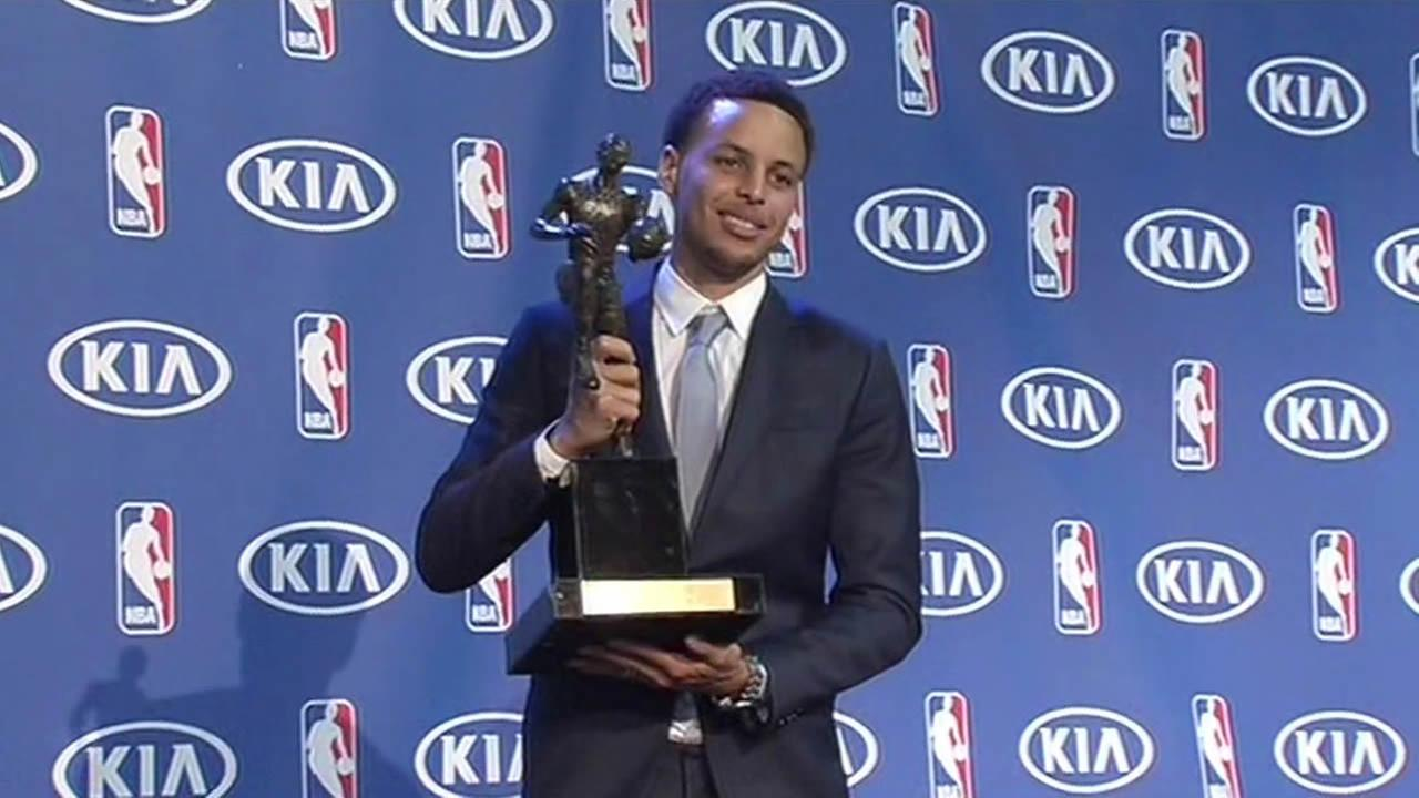 Golden State Warriors star Steph Curry smiles as he holds the NBAs Most Valuable Player award in Oakland, Calif. on May 4, 2015.