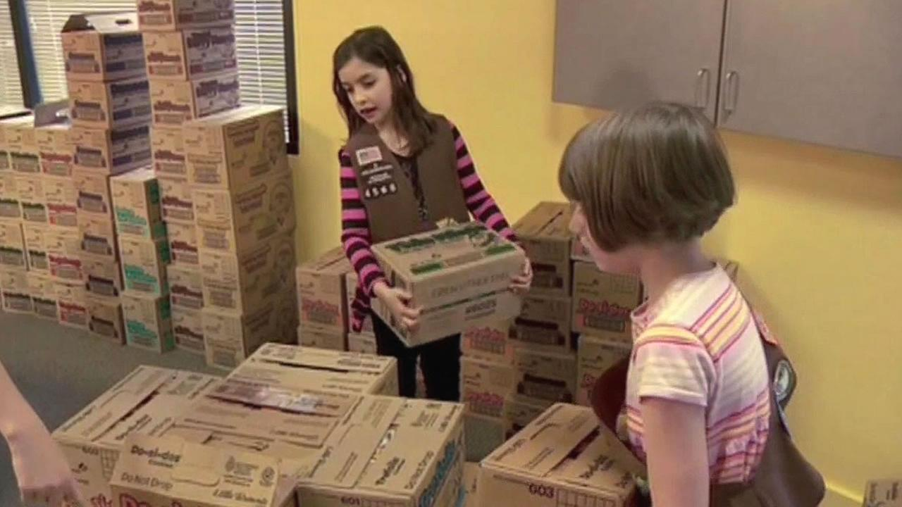 Two girl scouts stack boxes of cookies