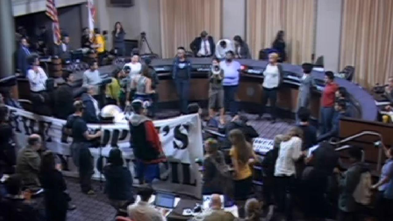 More than a dozen protesters have interrupted an Oakland City Council meeting meeting and have locked arms inside the city council chambers, May 5, 2015.