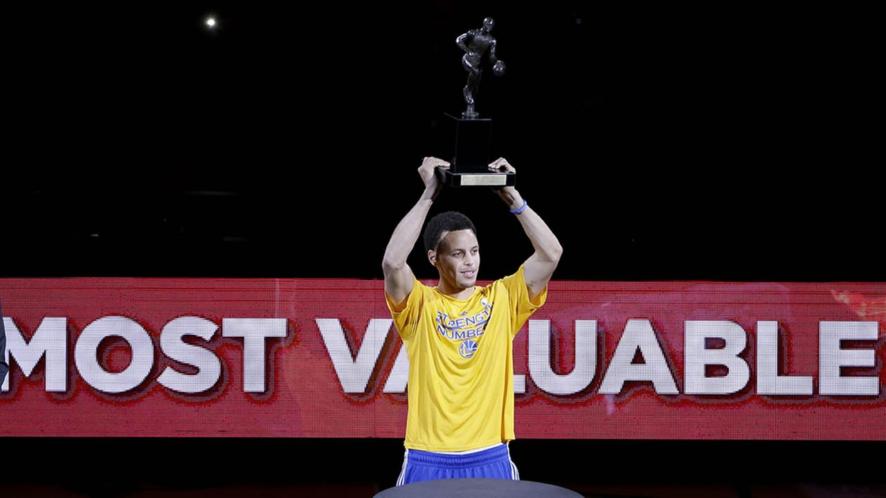 Golden State Warriors guard Stephen Curry holds the MVP trophy up for the crowd