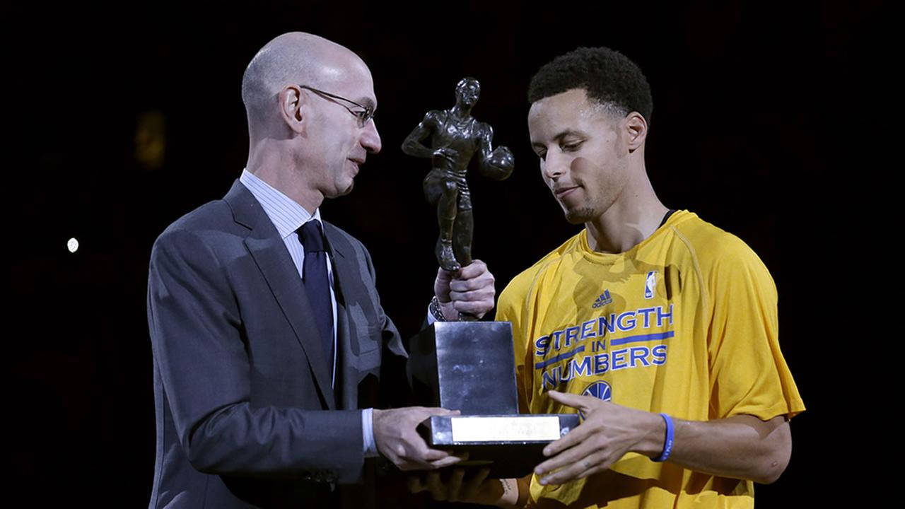 NBA commissioner Adam Silver gives Warriors guard Stephen Curry the MVP award