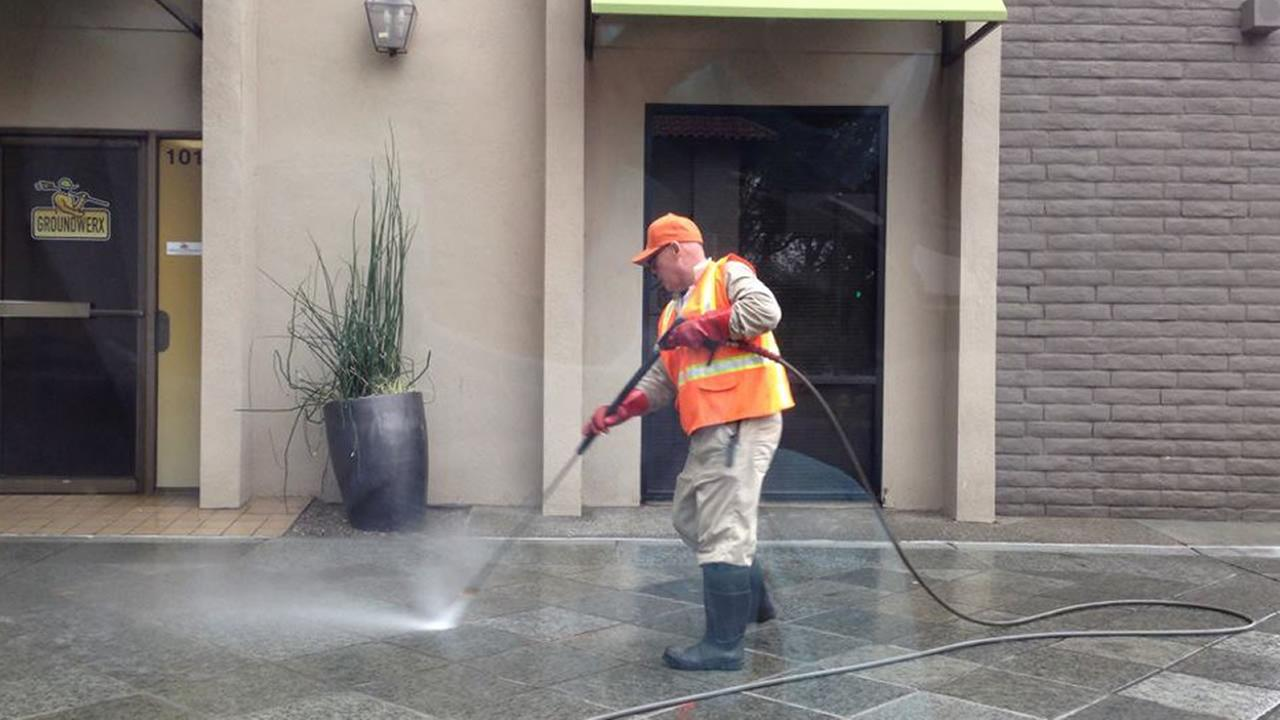 A city worker pressure washing the San Joses sidewalks.