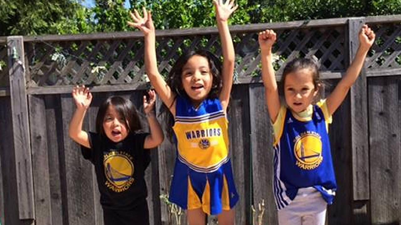 three little girls cheering for the Warriors