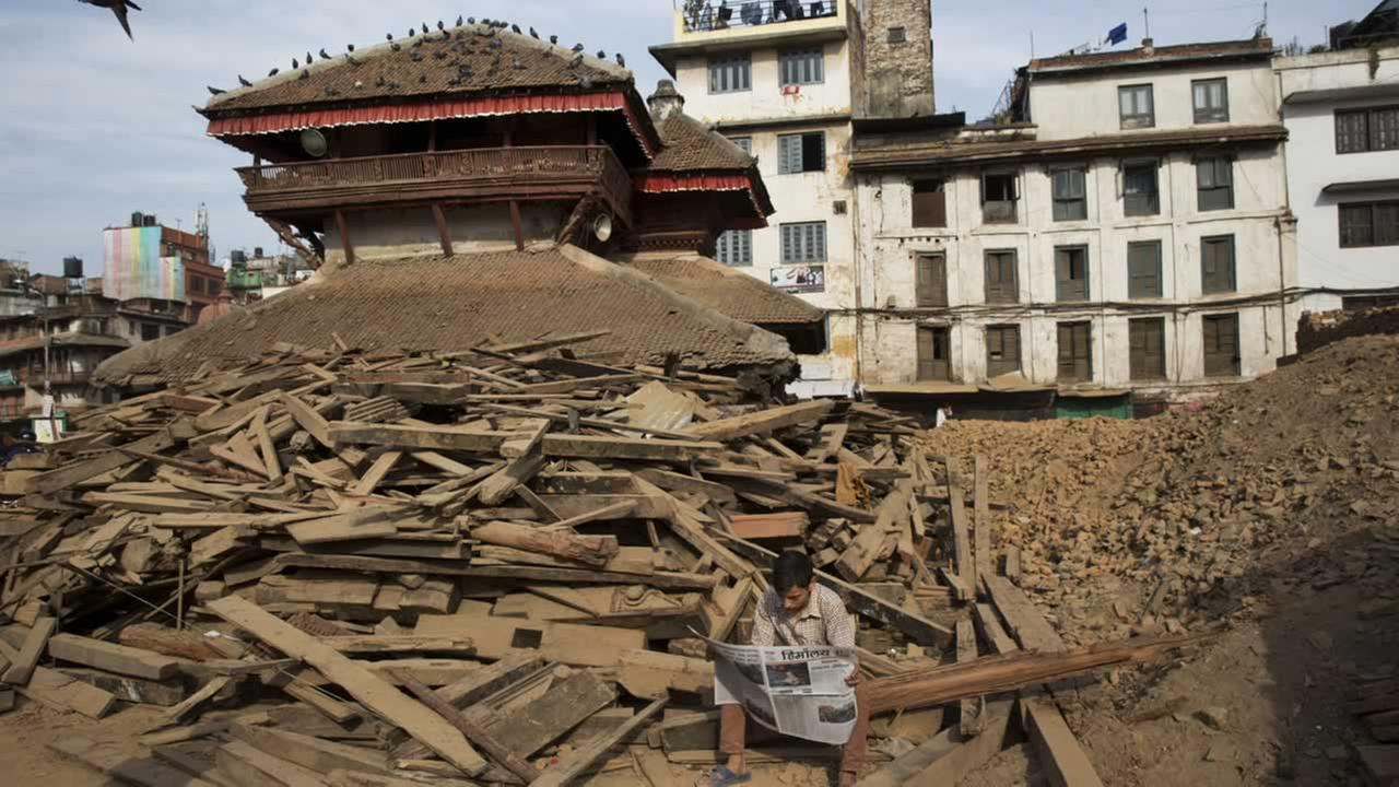 A man reads a newspaper at Basantapur Durbar Square, damaged in the April 25 earthquake in Kathmandu, Nepal, Tuesday, May 5, 2015.