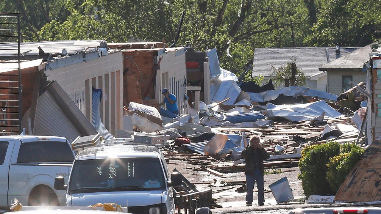 People look through rubble in an area damaged by severe weather in Oklahoma City, Thursday, May 7, 2015.