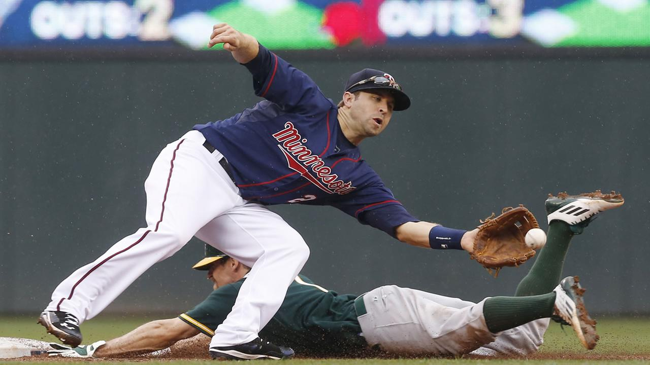 Oakland Athletics Billy Burns beats the throw to Minnesota Twins second baseman Brian Dozier to steal second base in the third inning of a baseball game, Thursday, May 7, 2015.