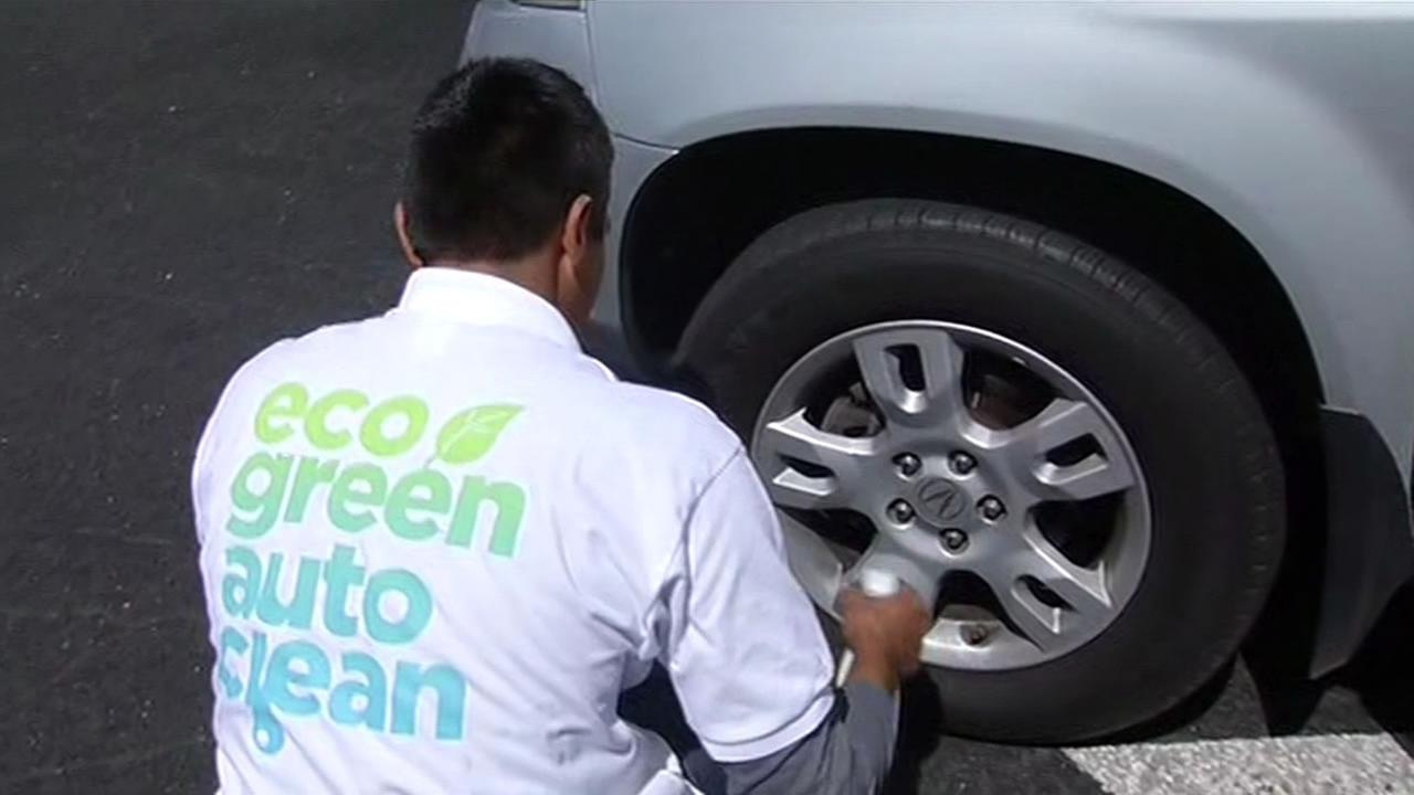 An employee with Eco Green Auto Clean washes a vehicle in Redwood City, Calif. on May 11, 2015.